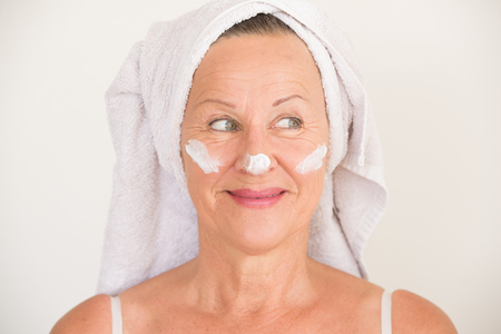 moisturiser: Portrait happy attractive mature woman with towel and protective skin care creme and moisturiser lotion on smiling face, bright background. Stock Photo