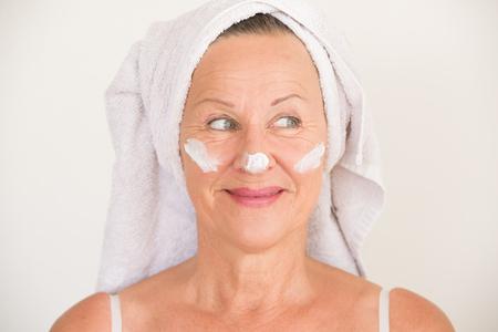 caras: Retrato feliz mujer madura atractiva con la toalla y crema de cuidado de la piel protectora y crema hidratante en la cara sonriente, fondo brillante. Foto de archivo