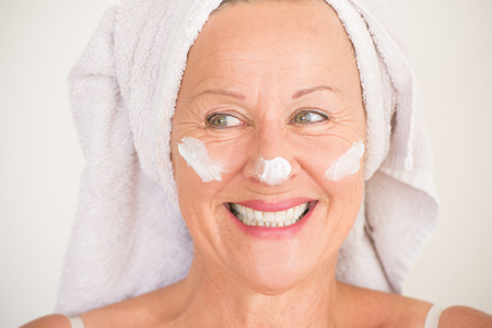 Portrait joyful attractive mature woman with towel and protective skin care creme and moisturiser lotion on happy smiling face, bright background. Stock Photo