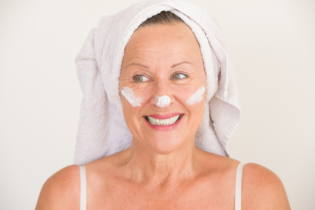 moisturiser: Portrait beautiful attractive mature woman with towel and protective skin care creme and moisturiser lotion on happy smiling face, bright background. Stock Photo