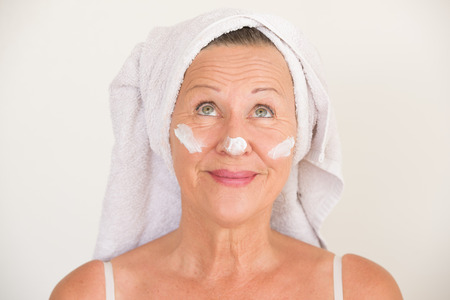 moisturiser: Portrait attractive mature woman with towel and protective skin care creme and moisturiser lotion on happy smiling face, bright background.
