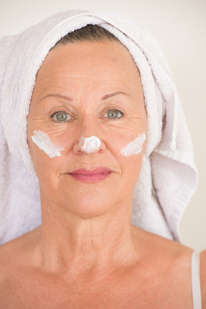moisturiser: Portrait attractive mature woman with towel and protective skin care creme and moisturiser lotion on smiling face, bright background.