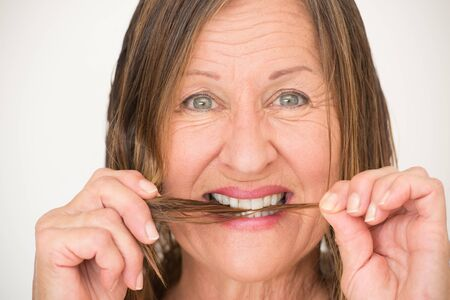 split ends: Portrait happy smiling attractive mature woman biting in split ends hair, bright background.