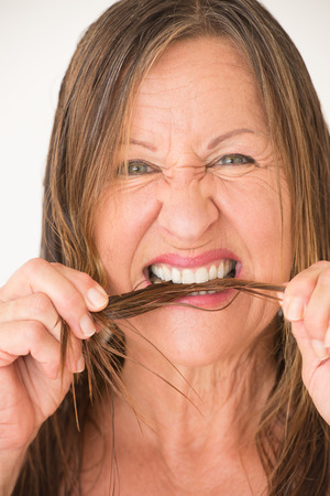 split ends: Portrait happy attractive mature woman biting in split ends hair, bright background. Stock Photo