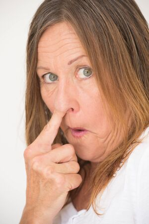 cheeky: Portrait ill mannered attractive mature woman picking nose with finger, cheeky happy smiling, bright background. Stock Photo
