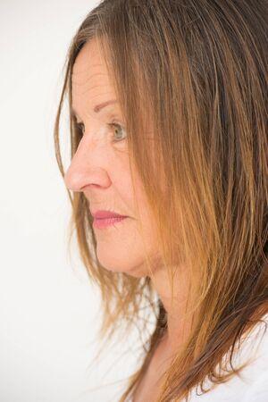 visage profil: profil Portrait attrayant femme mûre avec l'expression du visage grave, regard pensif solitaire, isolé, fond lumineux.