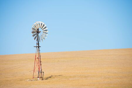outback australia: Iconic wind mill in outback Australia pumping up water on wheat farm in agricultural remote countryside, summer sunny blue sky and copy space. Stock Photo