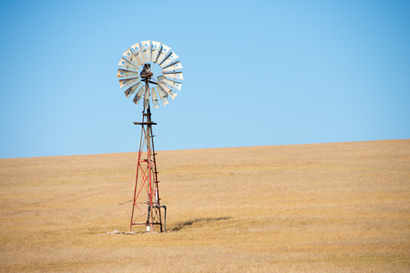 outback australia: Close Up spinning blades of Iconic wind mill in outback Australia pumping up water on wheat farm in agricultural remote countryside, summer sunny blue sky, copy space. Stock Photo