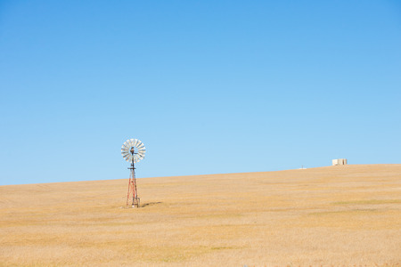 outback: Wind mill in outback Australia pumping up water on wheat farm in agricultural remote countryside, summer sunny blue sky and copy space. Stock Photo