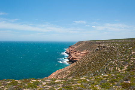 western australia: Scenic Aerial panorama of rough rock formation along coast of Kalbarri National Park in Western Australia, with wild waves of Indian Ocean crashing cliff, blue sky, horizon, copy space. Stock Photo