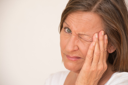 eye closed: Portrait angry upset attractive mature woman with painful migraine headache, one eye closed, isolated, bright background, copy space. Stock Photo
