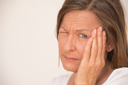 eye closed: Portrait upset attractive mature woman with painful migraine headache, one eye closed, isolated, bright background, copy space. Stock Photo