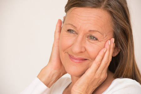 woman pose: Portrait confident relaxed retired mature woman posing happy smiling with hands on face, isolated, bright background.