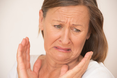 Portrait shocked attracive mature woman looking in disgust, stressed facial expression, isolated, bright background.