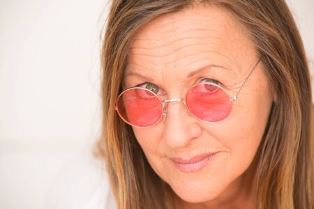 facial expression: Portrait relaxed attractive mature woman with confident happy look, red glasses, serious friendly facial expression, bright background.