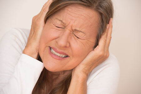 hands covering eyes: Portrait attractive mature woman in pain with migraine headache, covering ears with hands, closed eyes, isolated, bright background.
