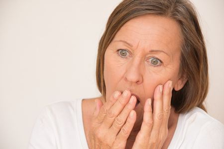 facial expression: Portrait shocked attractive mature woman with worried facial expression, scared, fear, anxiety, isolated, bright background. Stock Photo