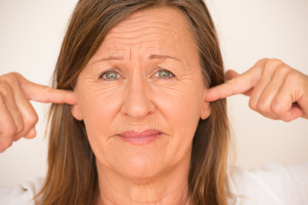 blocking: Portrait attractive mature woman blocking noise from ears with finger, stressed facial expression, isolated, bright background. Stock Photo