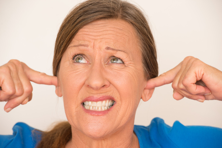 blocking: Portrait attractive mature woman blocking noise from ears with finger, worried facial expression, isolated, bright background. Stock Photo