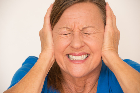 stress woman: Portrait attractive mature woman in pain with migraine headache, covering ears with hands, closed eyes, isolated, bright background.