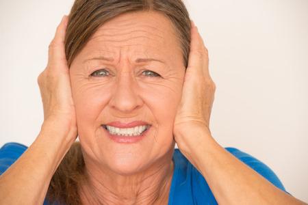 ruido: Retrato atractiva mujer madura en el dolor con la migraña, que cubre las orejas con las manos, aislado, fondo brillante.