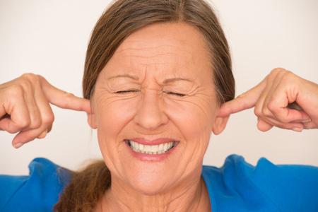 ruido: Retrato atractiva mujer madura que cubre el ruido de los oídos con los dedos, hizo hincapié en la expresión facial, los ojos, aislado, fondo brillante cerrado.