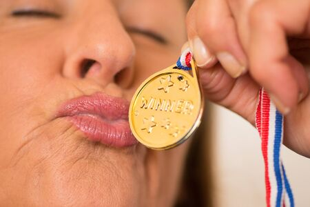 honour: Close Up Portrait proud active attractive mature woman kissing happy her winning gold medal award. Stock Photo