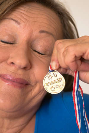 elderly adults: Portrait active attractive mature woman presenting proud with closed eyes her winning gold medal award.