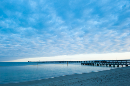 busselton: Busselton Jetty in Western Australia, longest timber pier in the Southern Hemisphere, at sunrise, with scenic cloudscape, peaceful Indian Ocean.