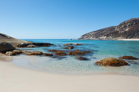 australia: Salmon Beach Bay in Torndirrup National Park near Albany, Western Australia, burnt vegetation on cliff coast, turqoise Southern Ocean, blue sky, copy space. Stock Photo