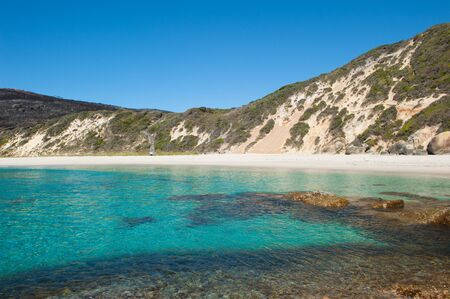 turqoise: Salmon Beach Bay in Torndirrup National Park near Albany, Western Australia, burnt vegetation on cliff coast, turqoise Southern Oean, blue sky, copy space.