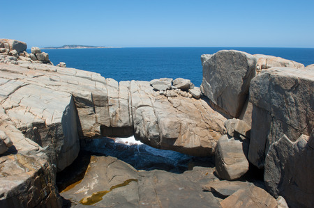 natural bridge: Beautiful scenic Natural Bridge rock formation in Torndirrup National Park, Albany, Western Australia, with cliff coast and Southern Ocean, blue sky, copy space.