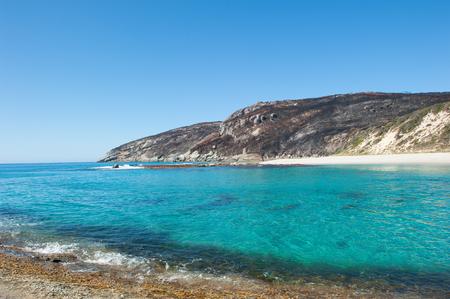 turqoise: Salmon Beach in Torndirrup National Park near Albany, Western Australia, burnt vegetation on cliff coast, turqoise Southern Ocean, blue sky, copy space.