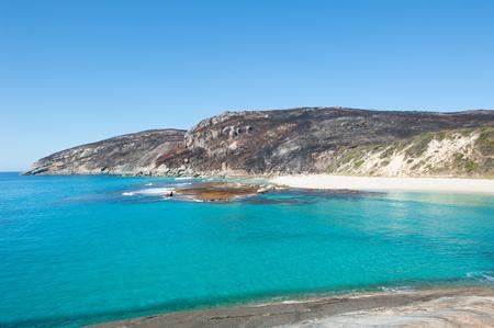 turqoise: Salmon Beach Bay in Torndirrup National Park near Albany, Western Australia, burnt vegetation on cliff coast, turqoise Ocean, blue sky, copy space.