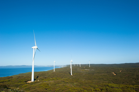 western town: Wind farm along coast of Southern Ocean in Western Australia, supplying renewable clean energy to town of Albany, summer sunny blue sky, copy space.