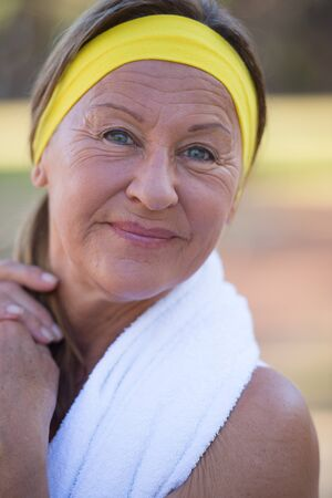 senior female: Portrait confident active fit sporty attractive mature woman, happy smile, towel, headband, exercising outdoors, blurred background.