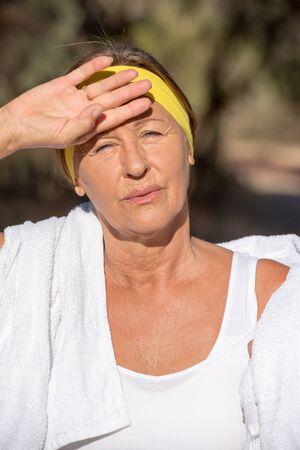 mujer alegre: Retrato activo ajuste deportivo atractiva mujer madura, agotado después de hacer ejercicio al aire libre, fondo borroso.