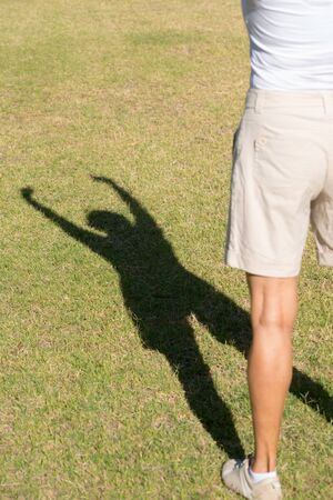 shadow silhouette: Portrait confident active fit sporty attractive mature woman exercising outdoors, winning pose as shadow silhouette on green grass in park, copy space.