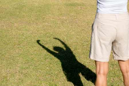 shadow silhouette: Portrait confident active fit sporty attractive mature woman exercising outdoors, winning pose as shadow silhouette on green grass, copy space.