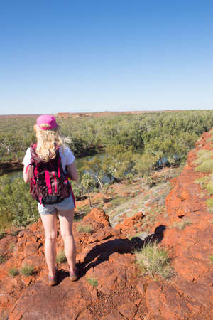 outback australia: Young blonde woman hiking in Millstream Chichester National Park in outback Australia, lookout at river, with rocks, trees, blue sky, copy space.