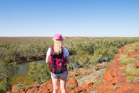 outback australia: Young blonde woman hiking in Millstream Chichester National Park in outback Australia, aerial panorama lookout at river, with rocks, trees, blue sky, copy space. Stock Photo