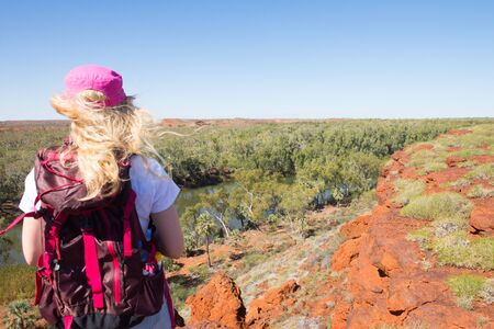 outback australia: Young blonde woman hiking in Millstream Chichester National Park in outback Australia, aerial lookout at river, with rocks, trees, blue sky, copy space. Stock Photo