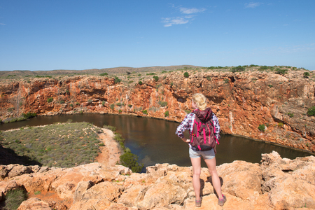 outback australia: Blonde woman hiking in outback Australia, overlooking Yardie Creek river in Cape Range National Park, Exmouth, summer sunny blue sky, copy space.