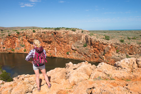 outback australia: Blonde woman hiking in outback Australia, panorama at Yardie Creek river in Cape Range National Park, Exmouth, summer sunny blue sky, copy space. Stock Photo
