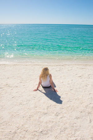 shark bay: Blonde young woman sitting relaxed at Shell Beach along lagoon of Shark Bay, Western Australia, summer sunny blue sky, copy space. Stock Photo