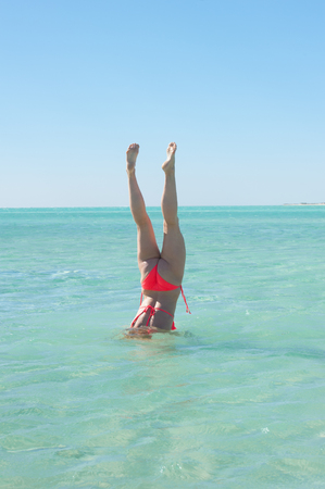 woman diving: Sporty active young woman in bikini doing diving underwater handstand in turquoise water at paradise tropical beach, legs up, summer sunny blue sky, copy space.