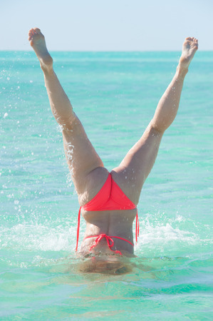 Active young woman in bikini doing diving underwater handstand in turquoise water at paradise tropical beach, legs up, summer sunny blue sky, copy space.