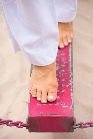 Close up female feet balancing on red metal bar over sand pit, blurred background. Stock Photo