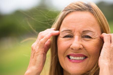 Portret vriendelijke ontspannen aantrekkelijke rijpe vrouw, gelukkig lachend, wind in de haren, handen omhoog gezicht, wazig buiten achtergrond.