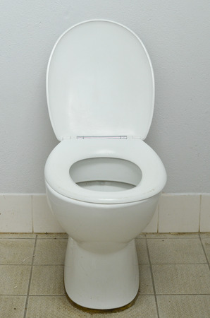 latrine: Filthy contaminated public water closet, with dirty tiles around bowl in messy restroom. Stock Photo